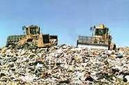 photo of two tractors on a huge heap of trash